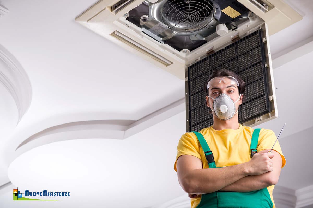 tecnico sanifica l'unità di condizionamento d'aria del soffitto